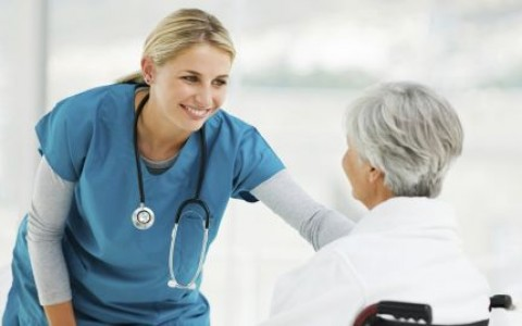Beautiful young female doctor talking to an elderly patient in a wheelchair. Horizontal shot.